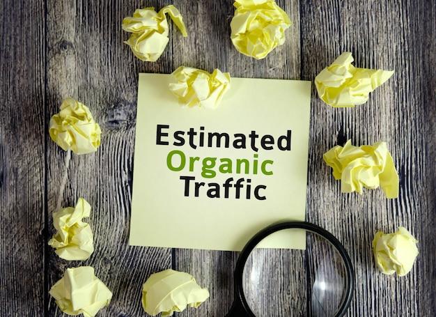Testo di traffico organico stimato su fogli di nota gialli su una superficie di legno scuro con fogli spiegazzati e una lente d'ingrandimento