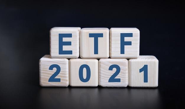 Testo etf 2021 su cubi di legno su sfondo nero con riflessione.