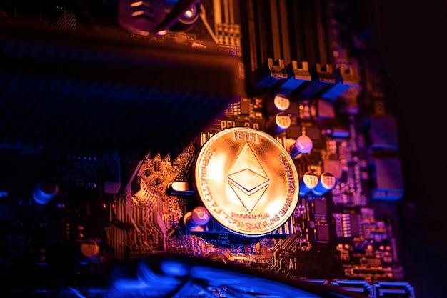Ethereum cryptocurrency coin su una scheda madre del computer pc, concetto di mining di criptovaluta.