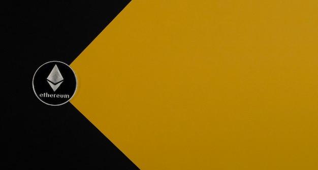 Ethereum o moneta d'argento eth su sfondo giallo con copia spazio per testo e raggio di luce. criptovaluta e concetto crittografico di etherum.
