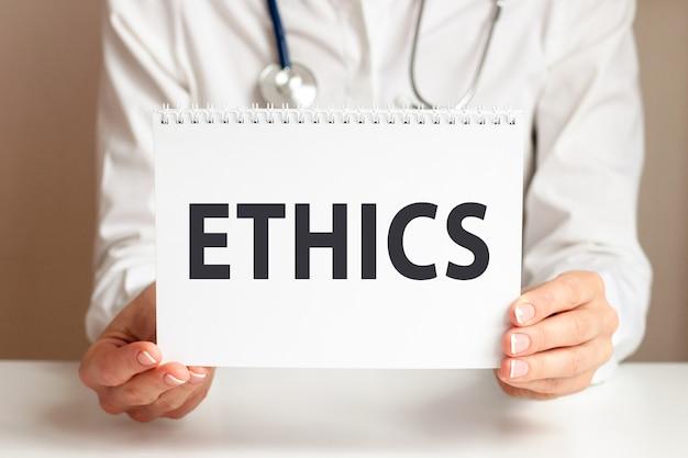Carta di etica nelle mani del medico. il medico passa un foglio di carta con testo etica, concetto medico.