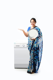 Donna asiatica indiana etnica o casalinga in sari o sari che mostra il piatto pulito con la lavastoviglie