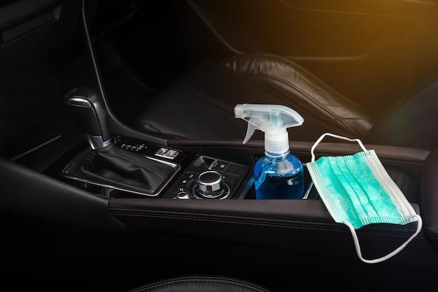 Gel per le mani con alcol etilico e maschera facciale per adulti posizionati sul seggiolino auto nel concetto di auto per covid-19