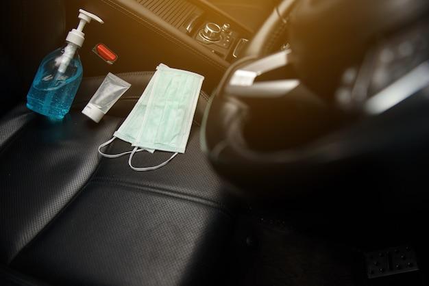 Gel per le mani con alcol etilico e maschera chirurgica posizionata sul seggiolino dell'auto in un'auto, concetto per il coronavirus, covid19