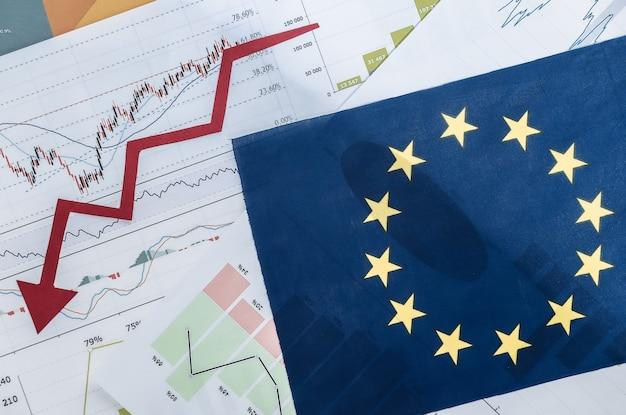 Bandiera dell'ue, freccia che cade verso il basso, grafici e tabelle. crisi economica globale