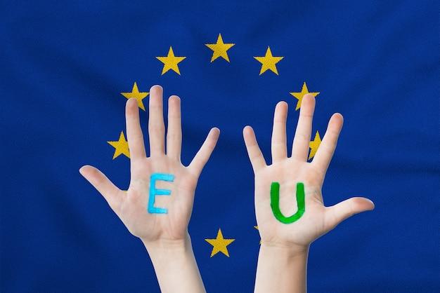 Iscrizione dell'ue sulle mani dei bambini contro la superficie di una bandiera sventolante dell'unione europea.