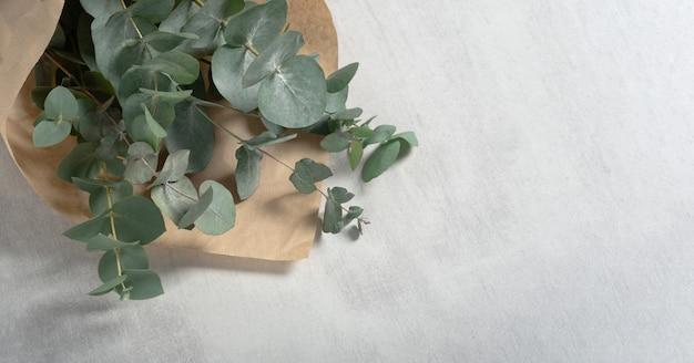 Mazzo di eucalipto in imballaggi di carta kraft su sfondo grigio chiaro di cemento con spazio di copia, vista dall'alto, piatto lay / congratulazioni per la festa della donna.