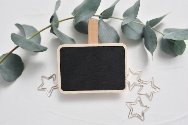 Ramo di eucalipto, decorazioni di stelle e tavola di legno con posto per il testo sul nero