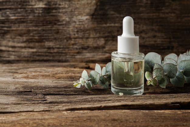 Olio essenziale di eucalipto e foglie fresche di eucalipto su legno