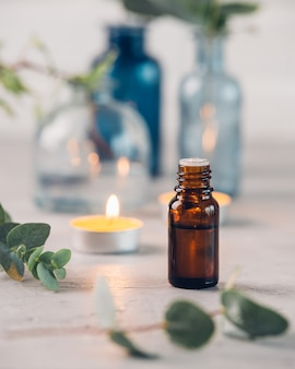 Olio essenziale di eucalipto e foglie fresche sulla tavola di pietra.