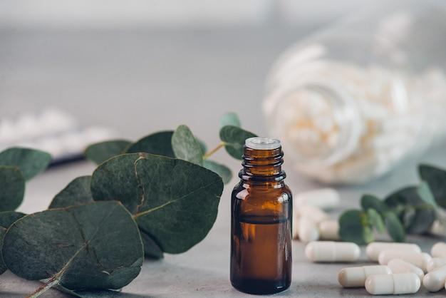 Olio essenziale di eucalipto e foglie fresche, capsule bianche pillole sulla tavola di pietra.