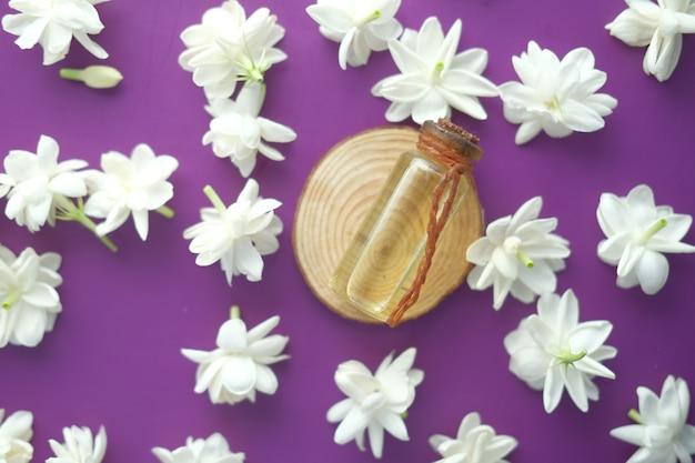 Oli essenziali di eucalipto in una bottiglia di vetro e fiori su viola