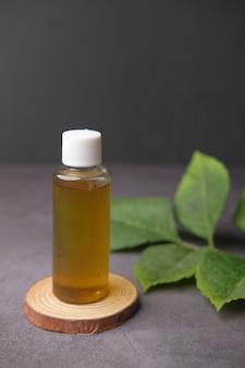 Oli essenziali di eucalipto in una bottiglia di vetro con foglia verde su fondo nero
