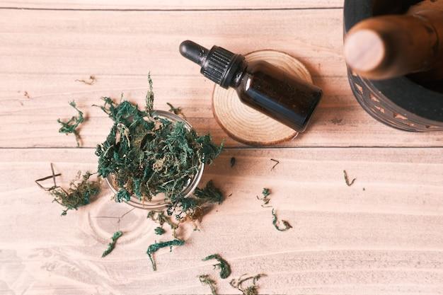 Oli essenziali di eucalipto in una bottiglia di vetro con foglia verde sul tavolo