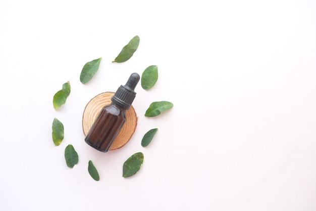 Oli essenziali di eucalipto in una bottiglia di vetro con foglia verde su piastrelle