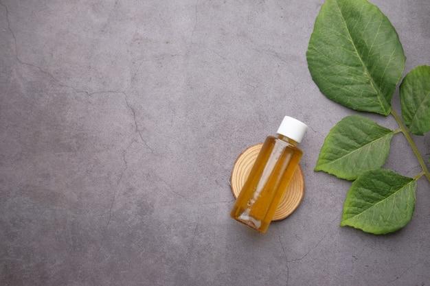 Oli essenziali di eucalipto in una bottiglia di vetro con foglia verde su superficie bianca