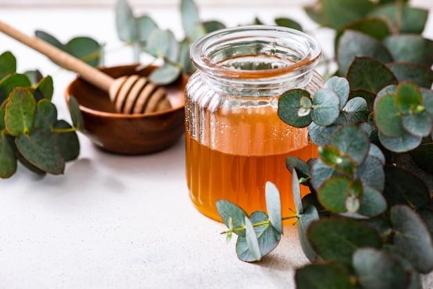 Foglie di eucalipto e miele in un barattolo di vetro come un concetto di cibo sano
