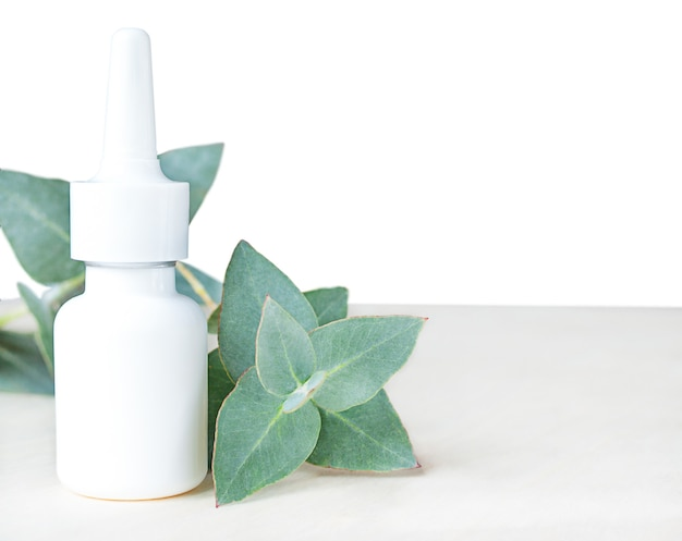Foglie di eucalipto e bottiglia bianca su superficie bianca.