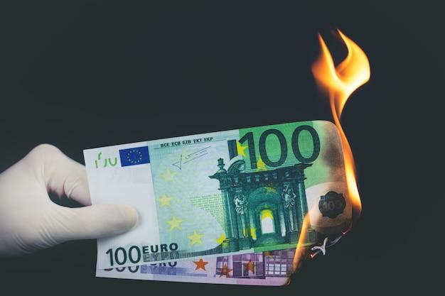 Le banconote in euro stanno bruciando su uno sfondo nero. concetto di fallimento.