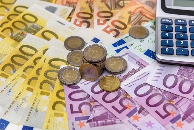 Banconote in euro come sfondo per monete e calcolatrice