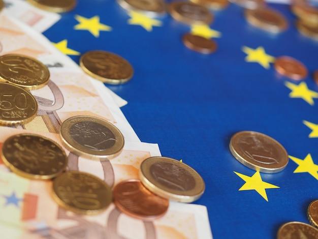 Banconote e monete in euro (eur), valuta dell'unione europea sulla bandiera dell'europa