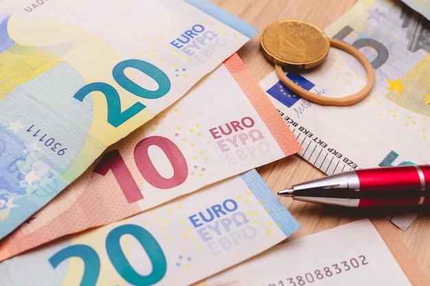 Le banconote in euro sul tavolo in primo piano con una moneta in euro nella composizione