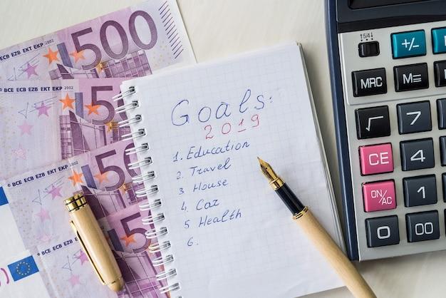 Banconote in euro con calcolatrice e blocco note con obiettivi