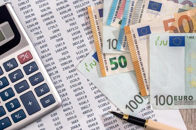 Banconote in euro con calcolatrice e penna sull'estratto conto bancario