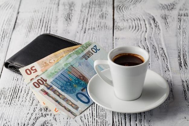 Euro fattura e tazza di caffè sulla tavola di legno. pagamento, mancia.