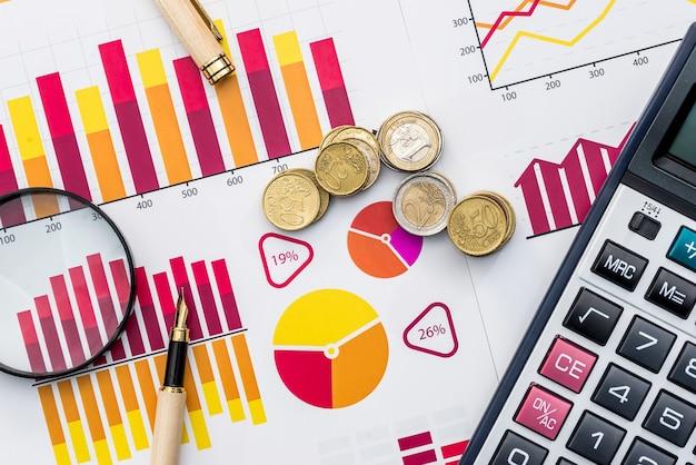 Monete in euro su sfondo di grafici commerciali con lente d'ingrandimento