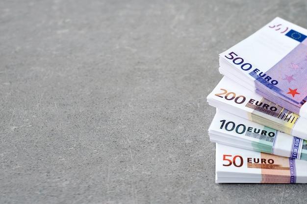 Soldi di valuta euro. denaro contante, banconote in euro. pile di banconote in euro su sfondo concreto in cinquecento, duecento, cento e cinquanta. copyspace per il testo.