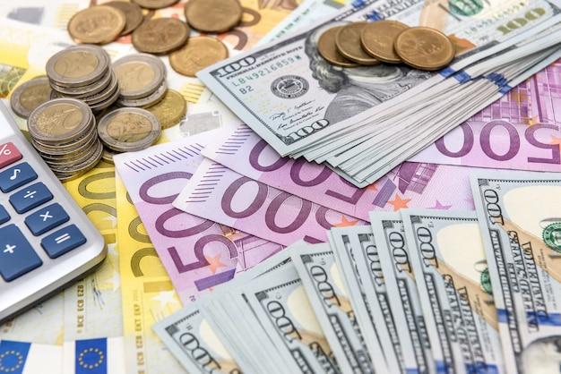 Banconote in euro e dollari come sfondo per monete e calcolatrice