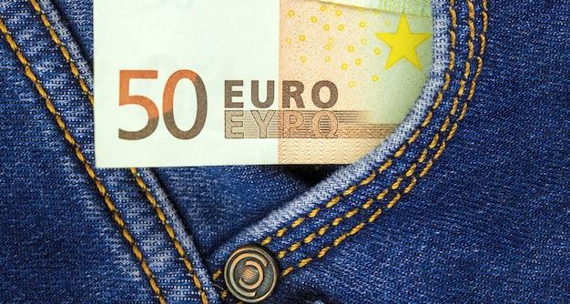Banconota da cinquanta euro in vista ravvicinata della tasca dei jeans blu, fondo di finanza aziendale