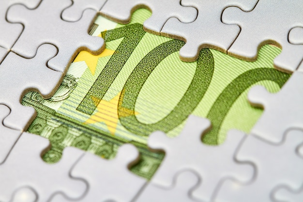 Euro puzzle, concetto di business della soluzione. banconote da cento euro e pezzi di puzzle. primo piano, messa a fuoco selettiva