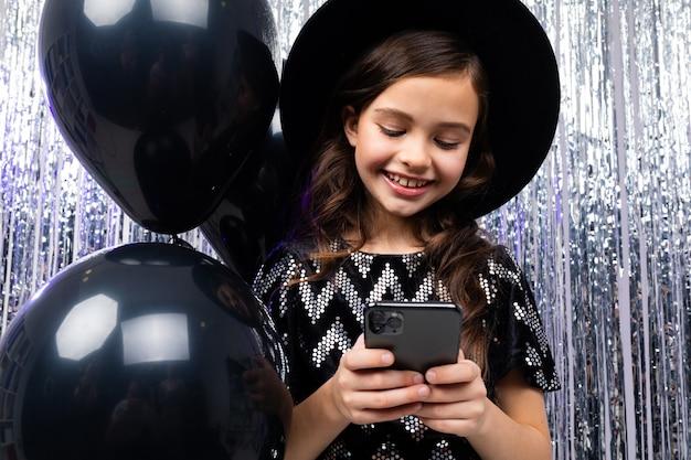 La ragazza europea di età scrive un messaggio al telefono per il suo compleanno su uno dei palloncini e tinsel neri dell'elio