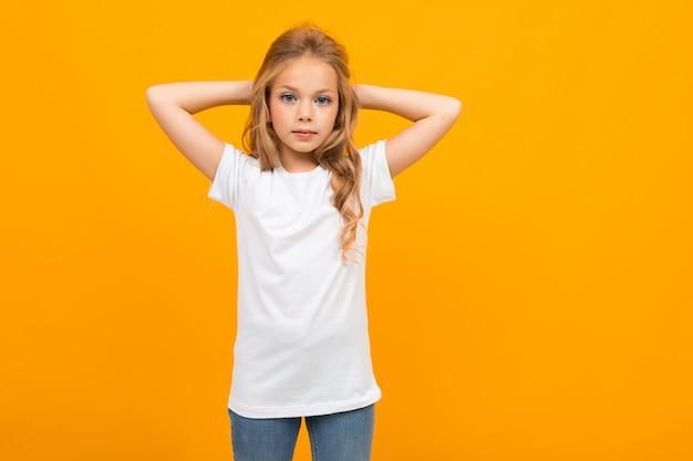 Ragazza attraente europea in una maglietta bianca con un modello su un giallo