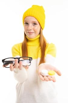 Ragazza dai capelli rossi attraente europea porge occhiali e lenti su uno sfondo bianco.
