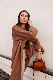 Bella giovane donna europea in cappotto lungo ed elegante in pantaloni beige alla moda con borsa alla moda marrone in pelle vicino a edificio vintage bianco. modello di moda ragazza elegante in posa all'aperto in strada.