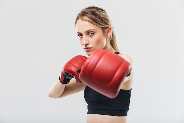 Donna bionda europea vestita di abbigliamento sportivo e guantoni da boxe che lavorano fuori e durante il fitness in palestra isolate su muro bianco
