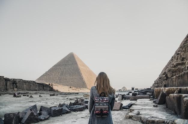 Una bionda europea cammina vicino alle piramidi nel deserto del cairo. la donna contro gli antichi edifici di giza.