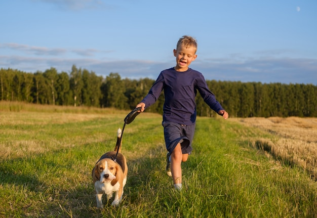 Ragazzo europeo che corre con un cane beagle al guinzaglio in estate sulla natura