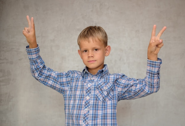 Il ragazzo europeo mostra il gesto di victoria con due mani sul muro grigio