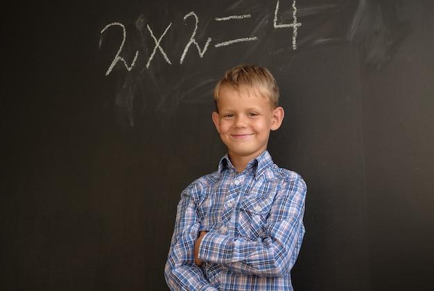 Studente ragazzo europeo pensa alla soluzione di problemi matematici, in piedi in un consiglio scolastico nero