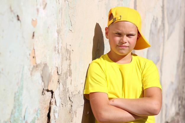 Un ragazzo europeo con una maglietta gialla e un berretto sta contro il muro sotto il sole splendente d'estate. foto di alta qualità