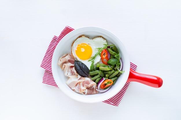 Colazione europea: uovo a forma di cuore, pancetta, fagiolini su un tavolo bianco. messa a fuoco selettiva. vista dall'alto. copia spazio.