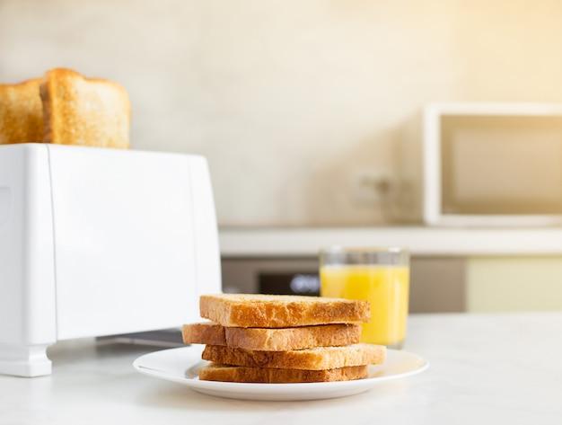 Colazione europea in cucina al mattino. tostapane elettrico bianco per il pane con succo d'arancia con toast.