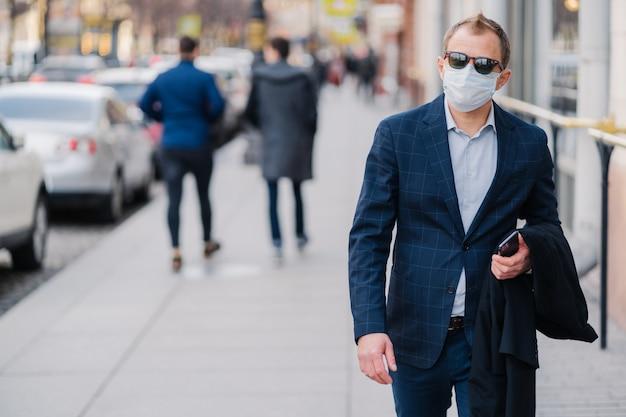 L'uomo d'affari europeo indossa abiti eleganti, occhiali da sole e maschera medica di protezione contro covid-19 o coronavirus, combatte contro i virus, cammina per la città affollata.