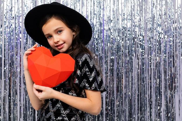 La ragazza sveglia europea in vestito e cappello da festa tiene un cuore di carta rosso su un brillante