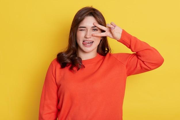 Signora europea dai capelli scuri con un'espressione divertente, in posa isolata sul muro giallo, che mostra la lingua, il viso accigliato, ammicca un occhio e ne copre l'altro con il segno v, gesto di vittoria.