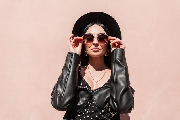 La donna europea alla moda indossa gli occhiali da sole vicino al muro rosa in una giornata di sole. la bella ragazza in vestiti neri di estate alla moda in elegante cappello alla moda posa vicino all'edificio. raggi di sole e signora di bellezza.